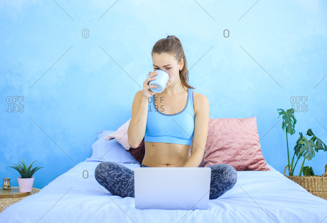 Young woman sitting on bed in workout clothes using laptop and drinking tea