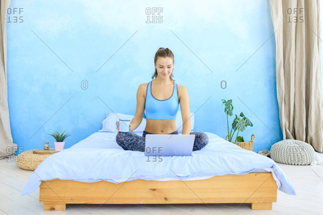 Young woman sitting on bed in workout clothes using laptop