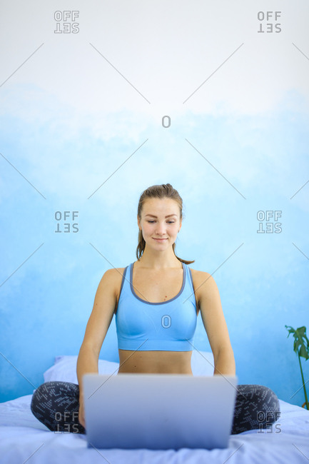 Woman sitting on bed in workout clothes using laptop