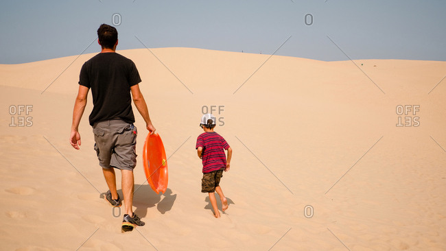 Father and son walking up sand dune with saucer for sledding