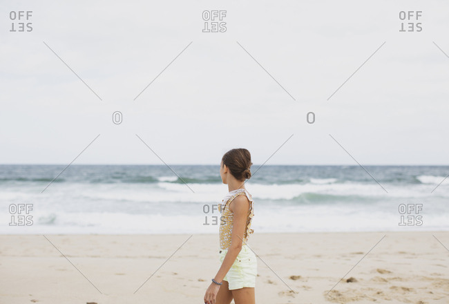 Girl standing on the beach looking at the sea