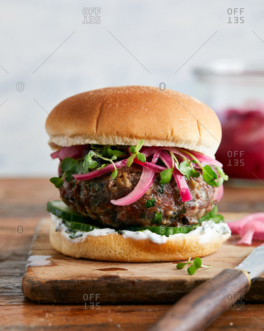 Close up of herb lamb burger with onions and tzatziki sauce on a wooden cutting board with a knife