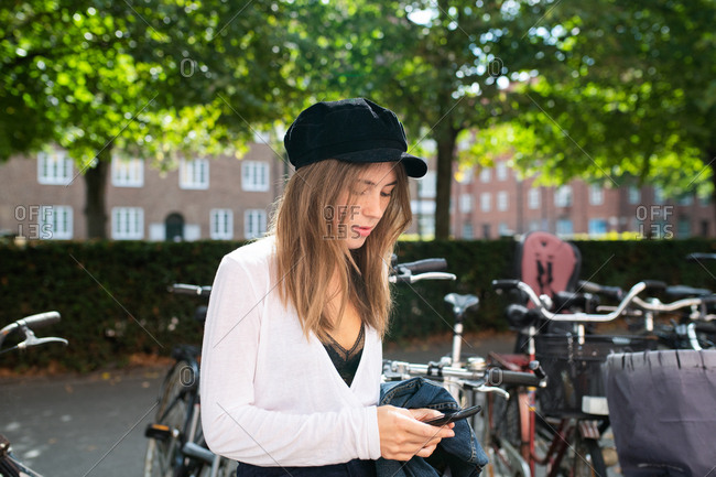 Young woman standing outside in front of bicycles using her phone