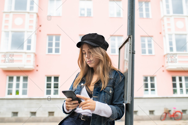 Young woman leaning against street sign using her phone