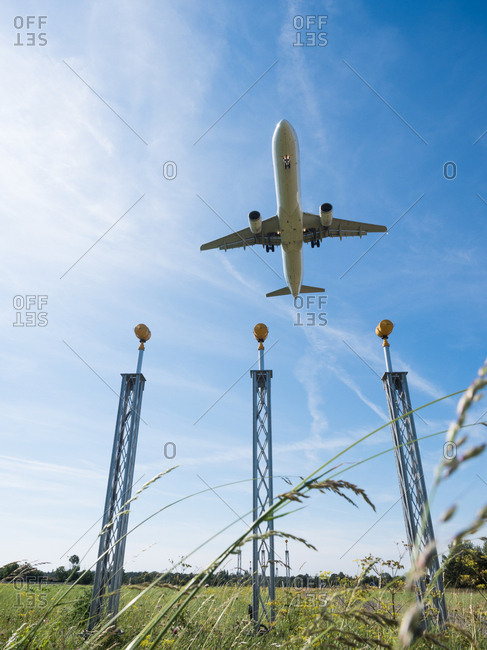 Underside view of airplane flying above approach lighting system at airport