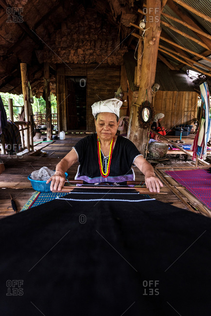Chiang Mai, Thailand - June 7 2018: Senior adult woman sitting and weaving dark cloths