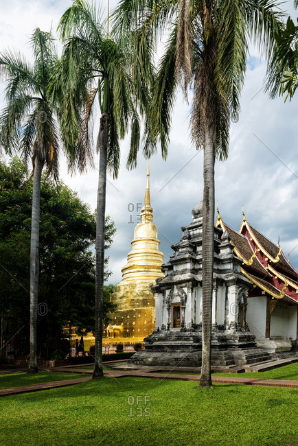 Stone oriental temple with gold statue under cloudy sky, Thailand