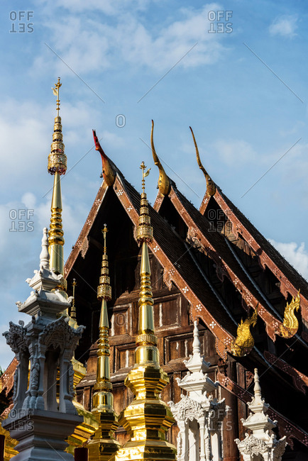 Exterior of ancient oriental temple with golden spires and roof under blue sky, Chiang Mai