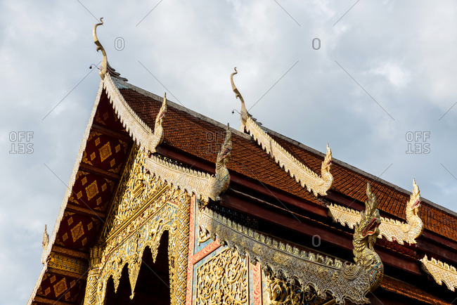 From below shot of golden design of beautiful temple with golden ornaments under cloudy sky, Chiang Mai