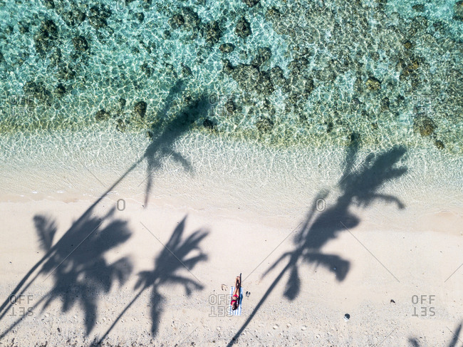 Woman sunbathing alone on an empty beach on a sunny day in Fiji