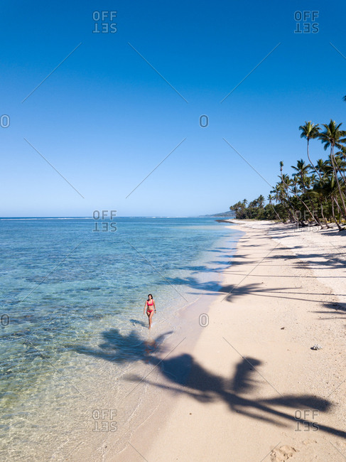 Girl wearing a red bikini walking on an empty beach on a sunny day in Fiji