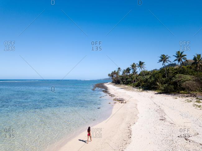 Girl wearing a red bikini walking on an empty beach on a sunny day in Fiji