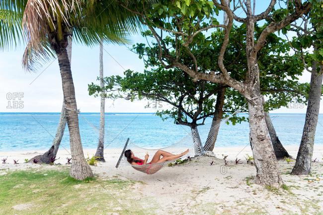 Beautiful woman with a red bikini reading on a hammock, Fiji