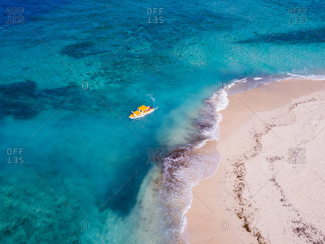 Aerial view of sand bank and a yellow boat