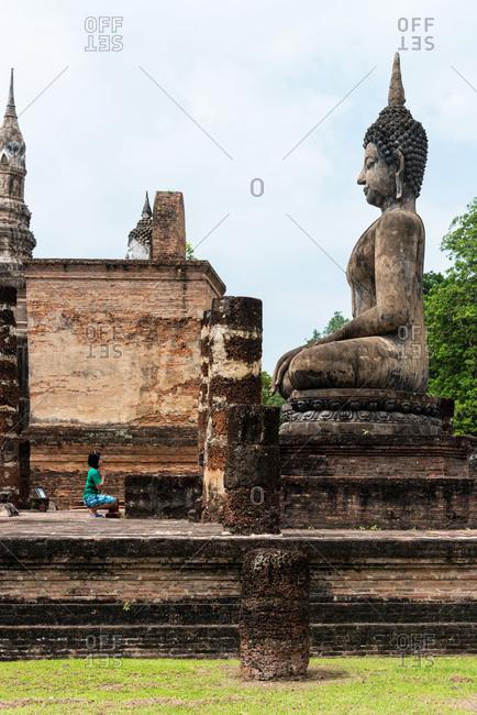 Sukhothai, Thailand - June 18, 2018: Woman praying in an ancient Buddhist temple in Sukhothai, Thailand