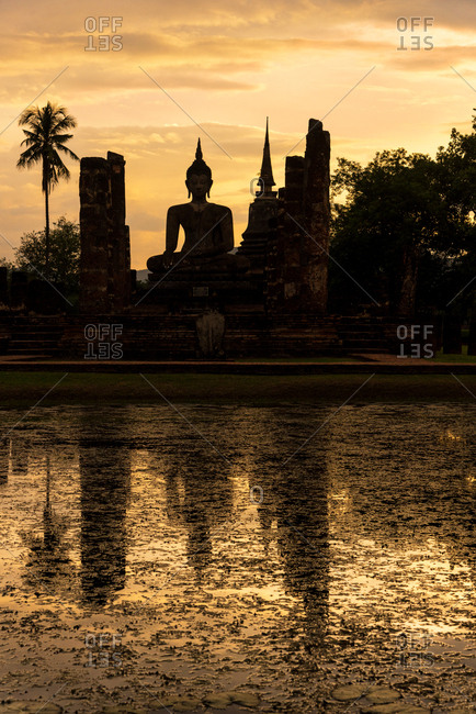 Reflection of an ancient Buddhist temple in Sukhothai at sunset, Thailand