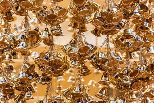 Hanging piles of golden bells in oriental temple in Chiang Mai, Thailand
