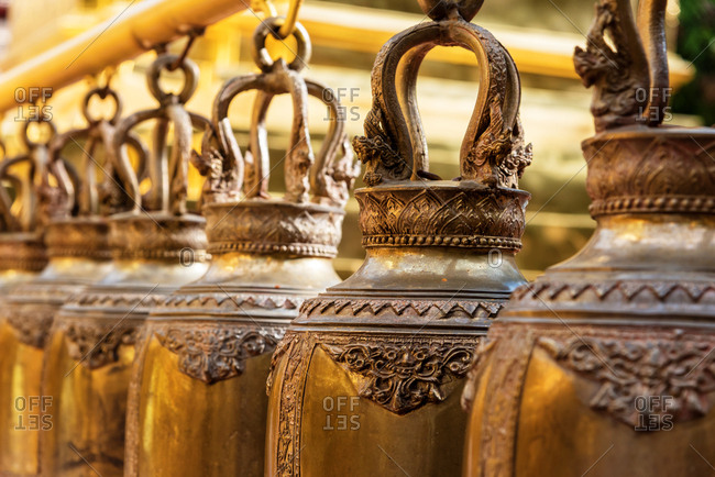 Ancient decorative bells with metal design hanging in temple in sunlight, Chiang Mai