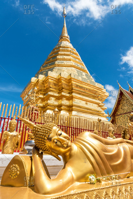 Chiang Mai, Thailand - June 7 2018: Bright and shiny golden statue of Buddha in beautiful oriental temple in Chiang Mai, Thailand