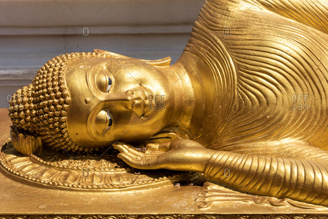 Beautiful ancient gold statue of lying Buddha shining in bright sunlight, Thailand