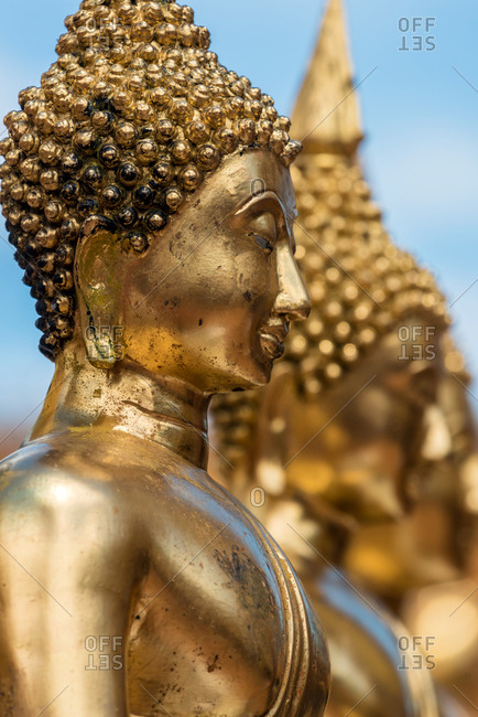 Bright shiny statues of golden Buddha placed in row, Thailand