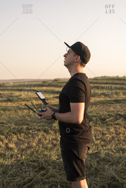 Man holding remote control for a drone in a field