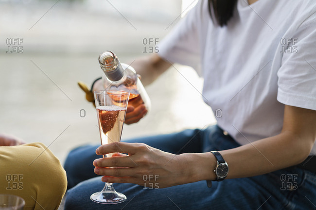 Close-up of woman pouring in sparkling blush wine