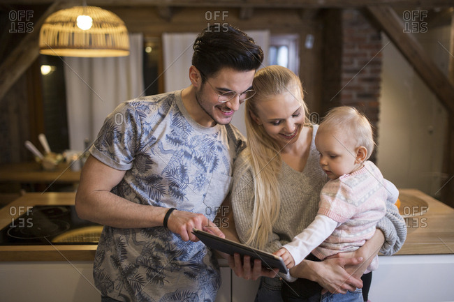 Happy young parents using tablet at home with their baby girl
