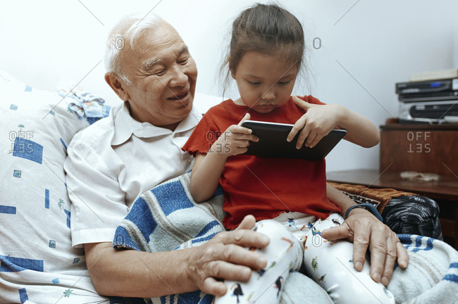 Grandfather and granddaughter with digital tablet at home