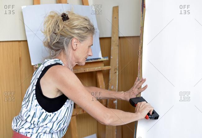 Female painter in her atelier- stapling paper on easel