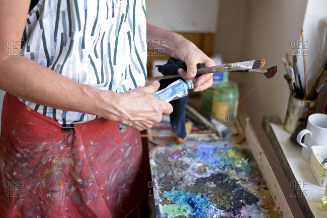 Female painter in her atelier- paint tube and paintbrushes