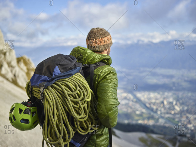 Austria- Innsbruck- Nordkette- man with rope and climbing equipment looking at view