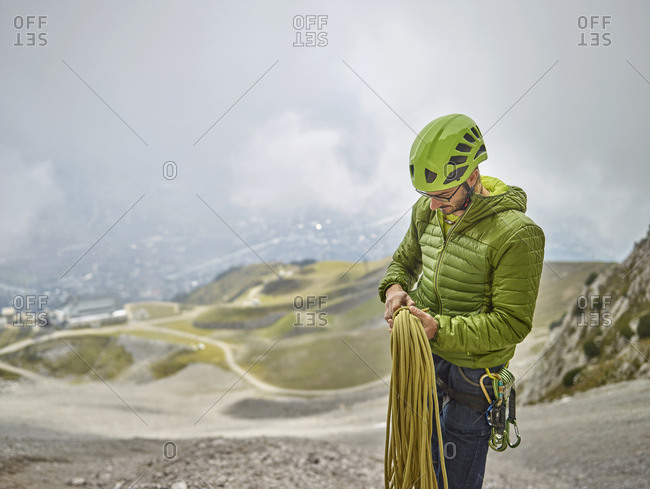 Austria- Innsbruck- Nordkette- man with rope and climbing equipment