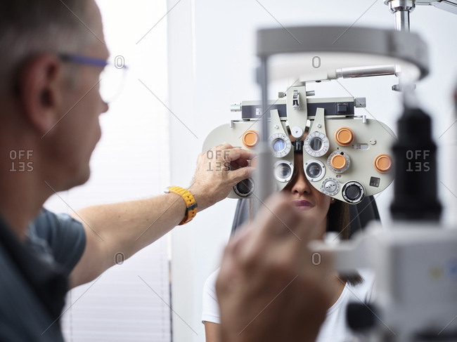 Optometrist examining young woman's eye