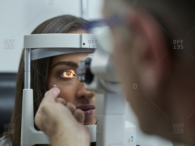 Optometrist examining young woman's eye- contact lens on index finger