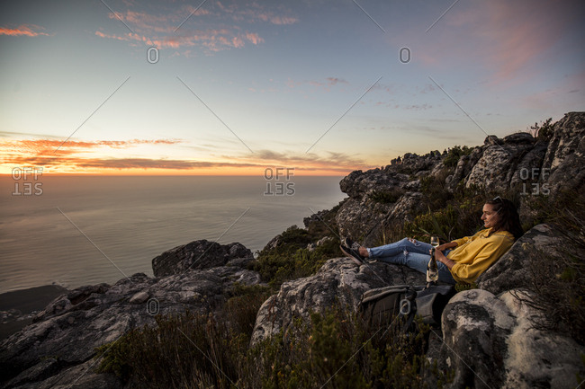 South Africa- Cape Town- Table Mountain- woman sitting on a rock drinking wine at sunset