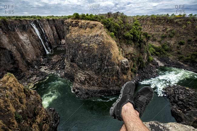 Zimbabwe- legs of a man resting at Victoria Falls