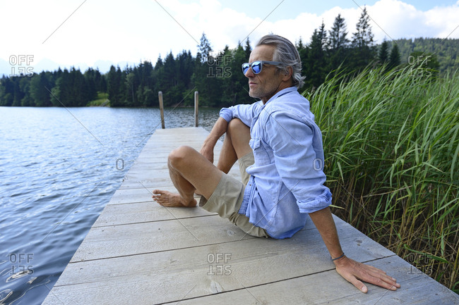 Germany- Mittenwald- mature man relaxing on jetty at lake