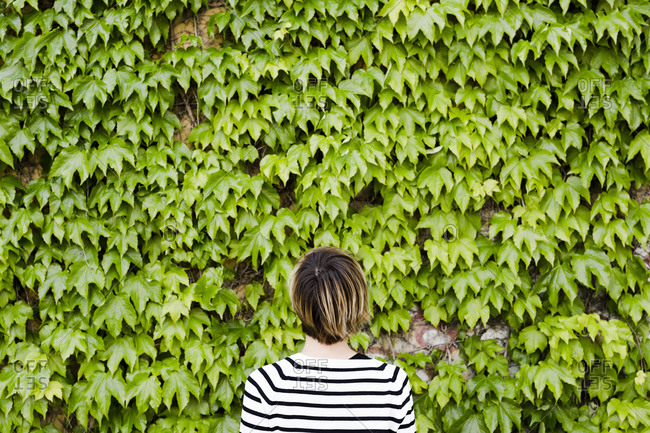 Back view of woman in front of facade greenery