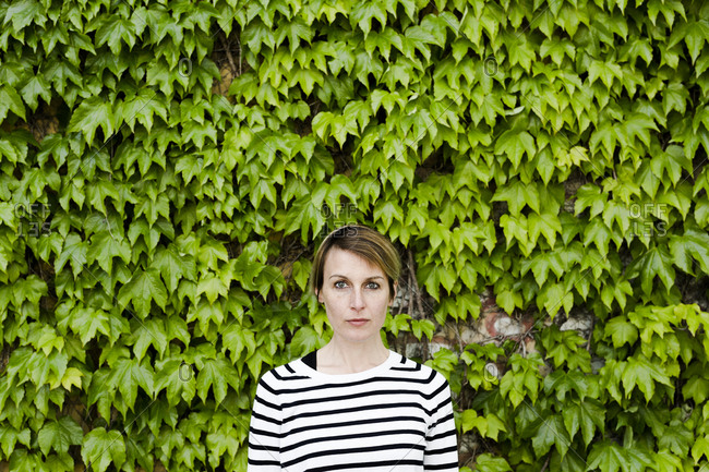 Portrait of woman in front of facade greenery