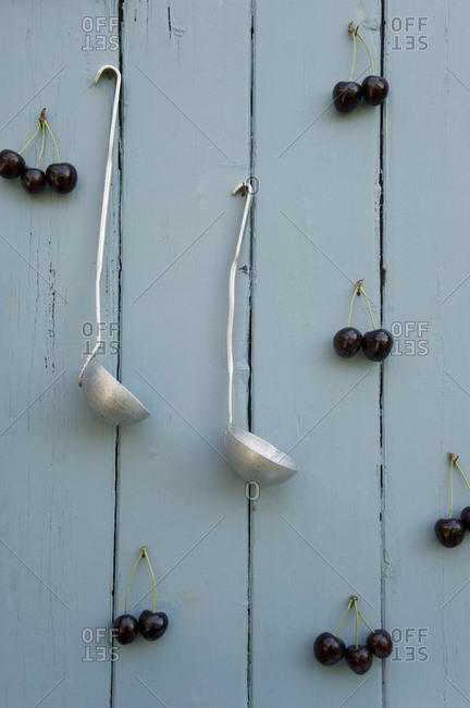 Cherries and two ladles hanging on wooden wall
