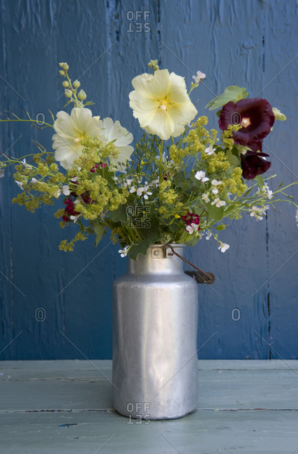 Bunch of wildflowers in milk can