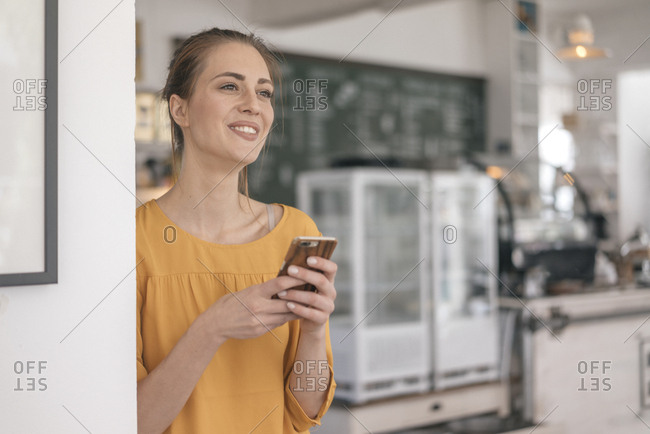 Young business owner standing in her coffee shop- using smartphone