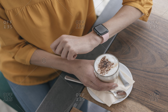 Woman wearing smartwatch- sitting in cafe- drinking coffee
