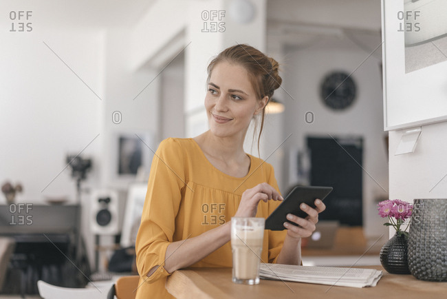 Young woman working in coworking space- using digital tablet