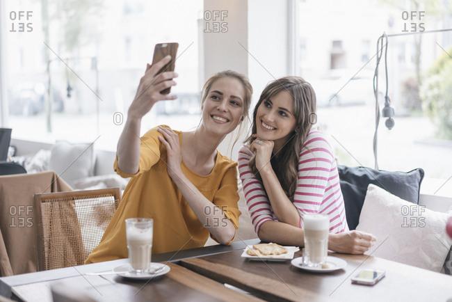 Two girlfriends meeting in a coffee shop- taking selfie