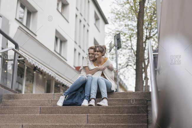 Friends sitting on stairs in the city- sharing cardigan