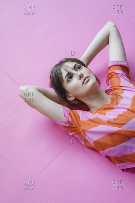 Woman lying on pink background with hands behind head- thinking