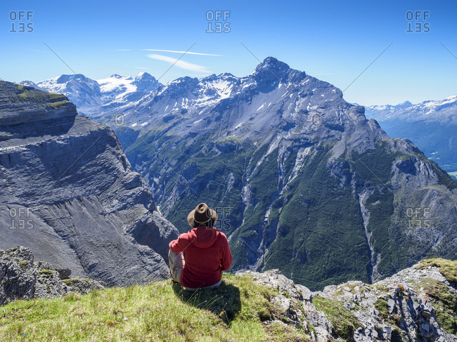 Italy- Lombardy- Sondrio- hiker resting with view to Stelvio Pass and Ortler