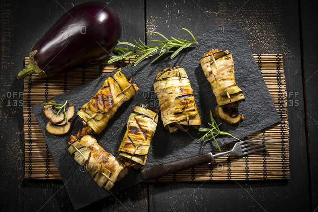 Grilled aubergine slices stuffed with mincemeat- champignons and goat cheese on slate